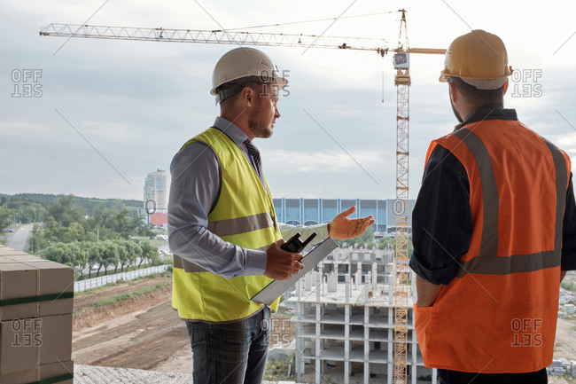 Rear view of inspector and general foreman standing on construction site, watching building process and talking, tower crane in the background