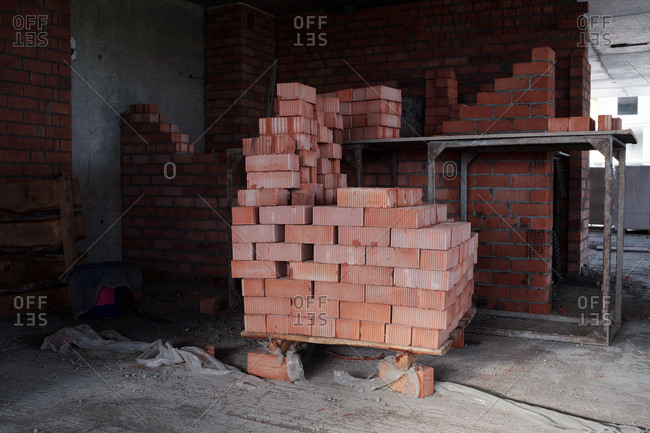 Construction material. Horizontal shot of new red bricks stacked in empty  building under construction