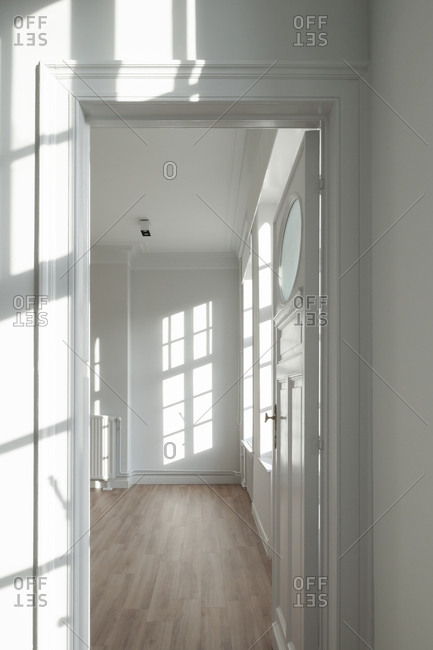 Sunlight shining through windows in room with open door inside home