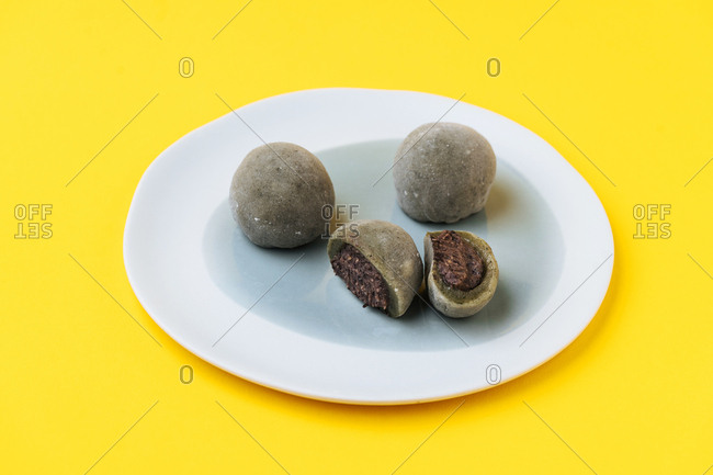Mochi Japanese dessert whole and cut in half on yellow background