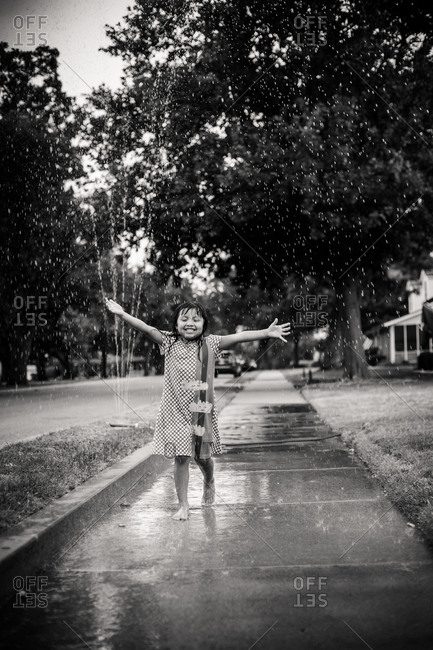 Young girl playing in the sprinklers on a suburban sidewalk