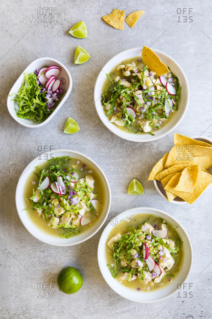 Overhead view of bowls of pozole and tortilla chips