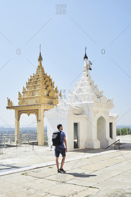 Caucasian solo traveler exploring golden and white prayer rooms at the top of Mandalay hill Mandalay, Myanmar