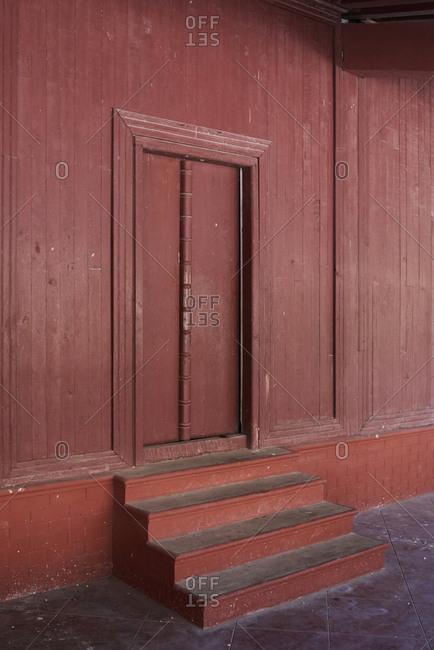 Closed doors in burgundy color Architecutre details Royal Palace, Mandalay, Myanmar