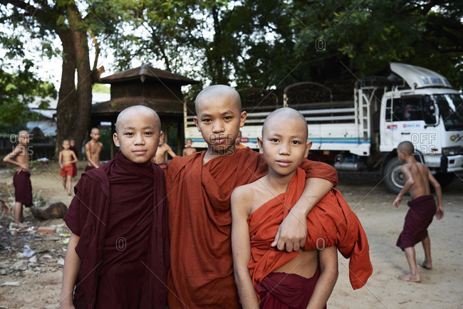 Amarapura, Myanmar - November 11, 2017: Portrait of three burmese novice monks looking at camera embracing each other Friendship