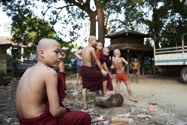 Amarapura, Myanmar - November 11, 2017: Group portrait of burmese novice monks relaxing outside monastery at sunset
