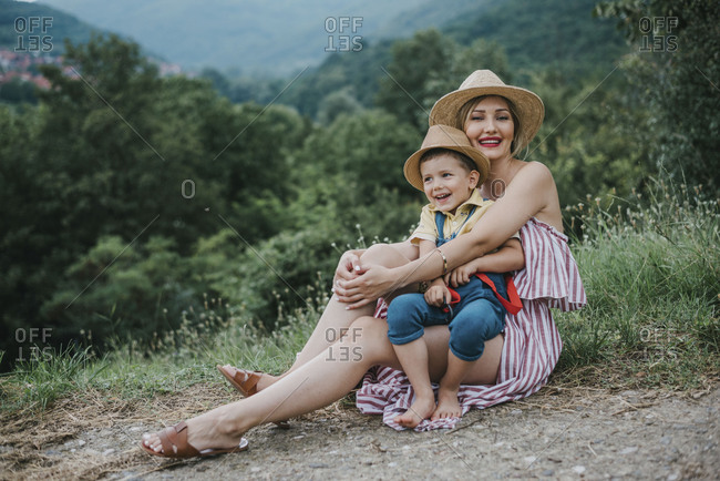 Young smiling mom sitting on a ground and holding her little kid among the grass in nature