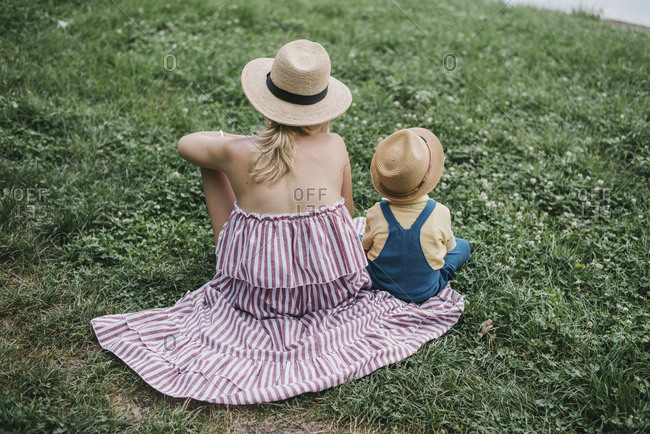 Young boy sitting on his mothers dress - Mother and son enjoying their time in nature