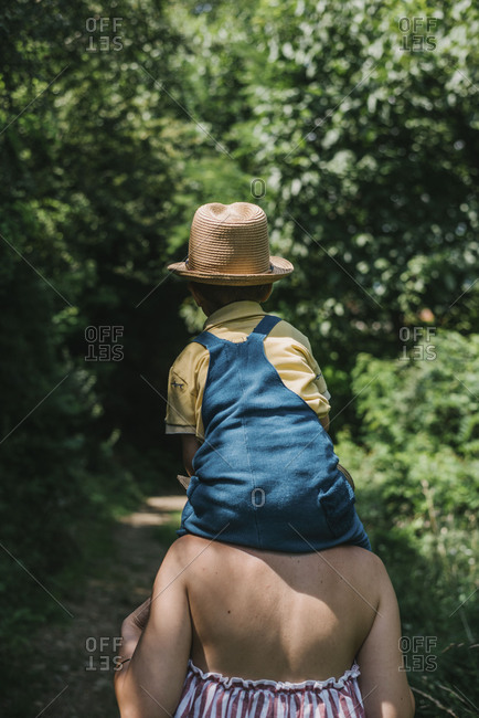 Little boy with a hat sitting on his mothers shoulders while walking through the forest