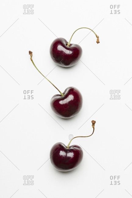 Top view of three cherries on white background