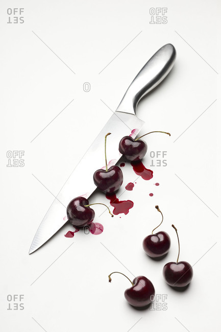 Top view of three cherries stuck in a knife on white background