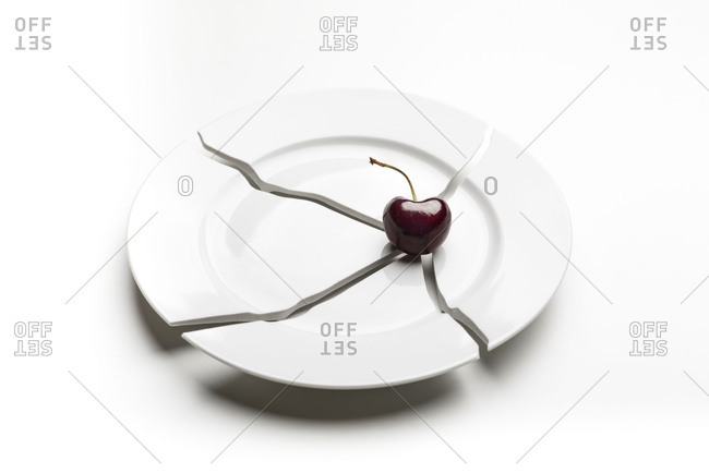 Cherry on broken plate and white background