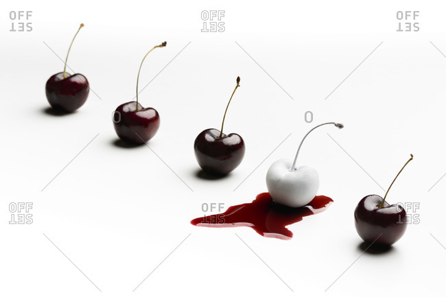 Row of red cherries, one of them white on its juice