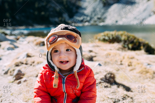 Happy baby girl in the mountains wearing aviator hat
