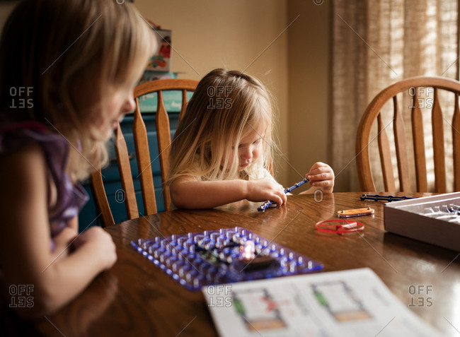 Two girls playing game on table