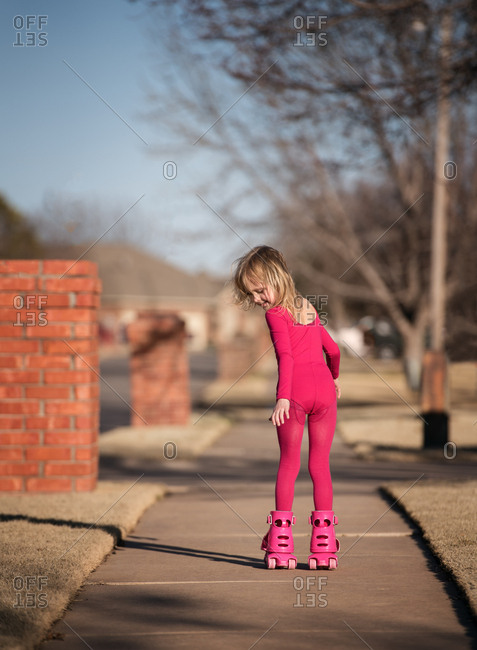 Blonde girl in pink outfit riding roller skates