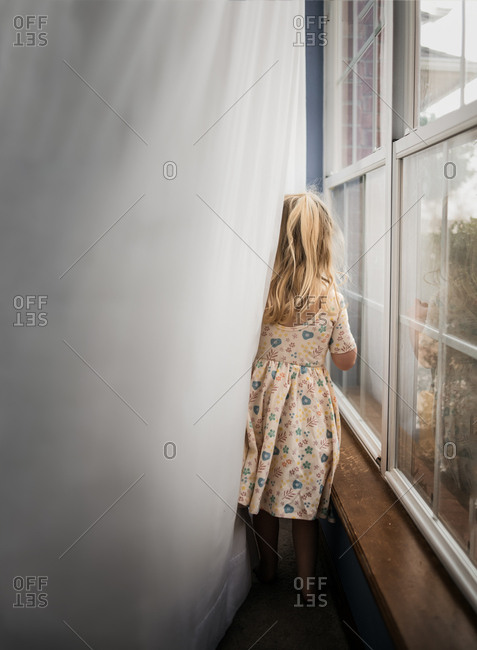 Rear view of girl playing in curtains
