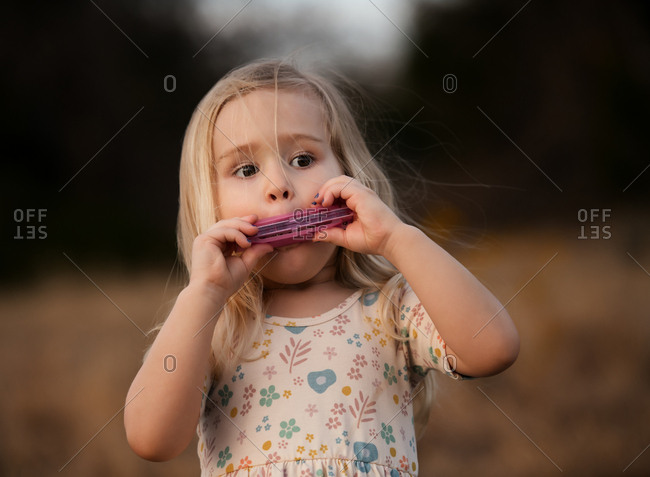 Young blonde girl playing a harmonica