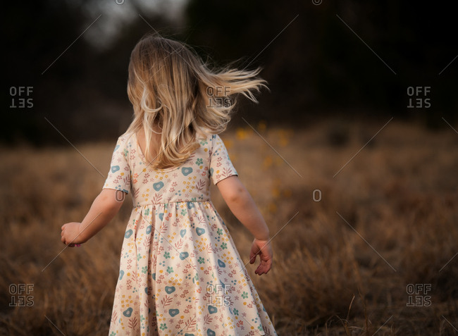 Rear view of young blonde girl playing in a field