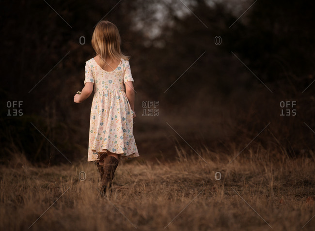 Rear view of young blonde girl walking in a field