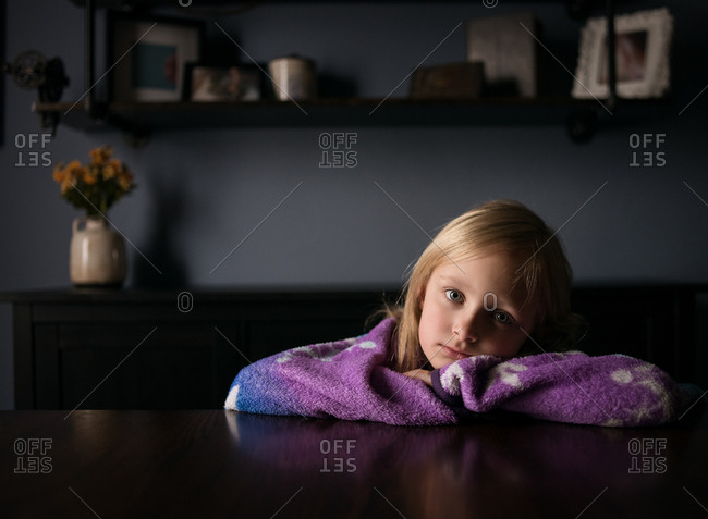 Blonde girl wrapped in a blanket resting at dining room table