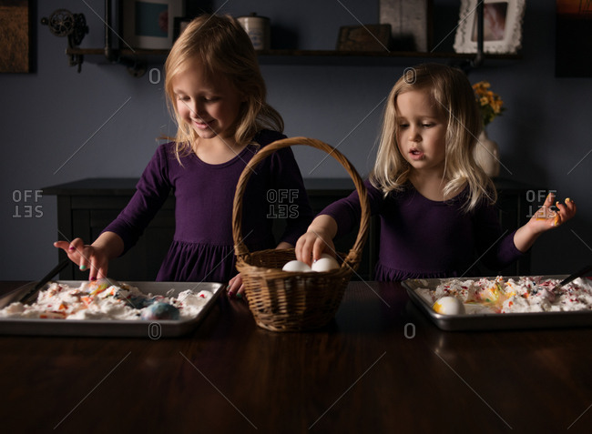 Two girls dying Easter eggs with cream