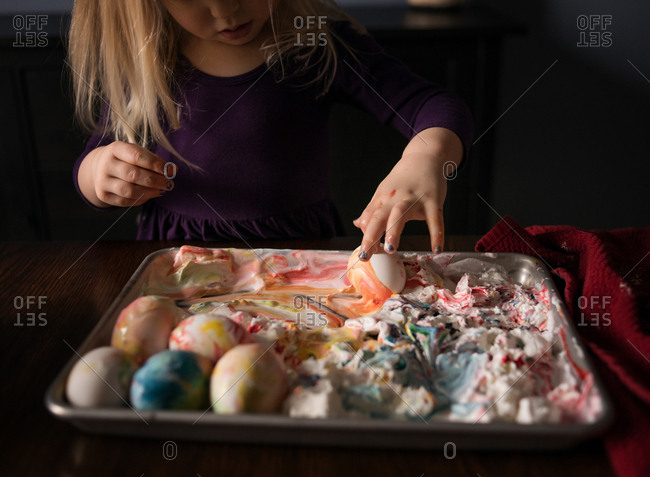Girl dying Easter eggs with cream