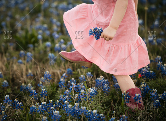 Little girl wearing pink dress and boots holding flowers in a field