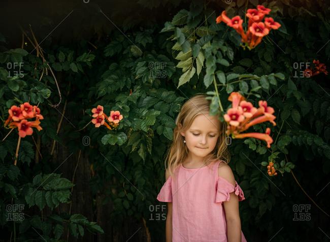 Blonde girl standing by orange flowers