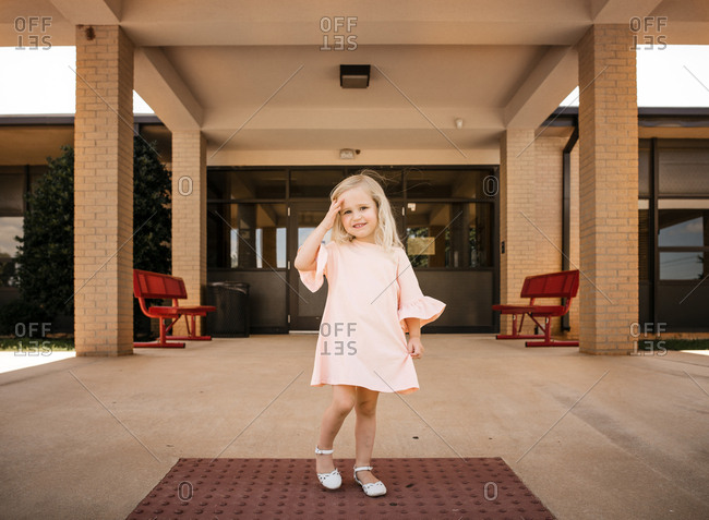 Blonde girl in pink dress standing in front of building