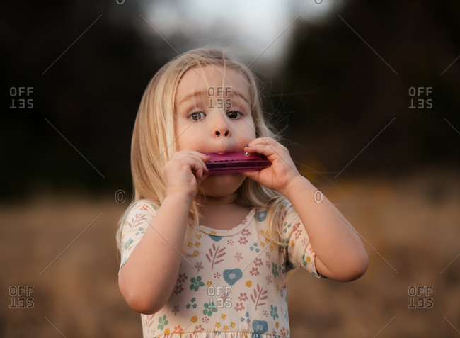 Little blonde girl playing a harmonica