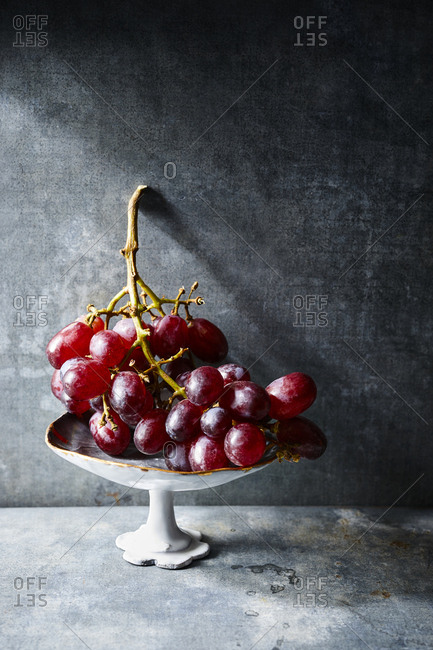 Red grapes on a vine on gray background