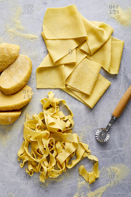 Homemade pasta on marble surface and cutting tool