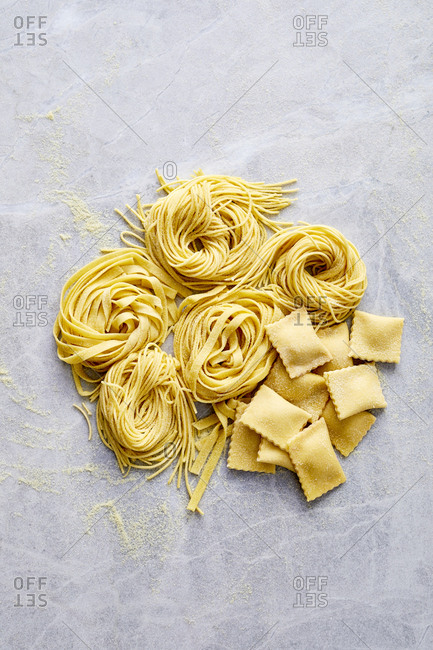 Spaghetti, fettuccine and ravioli noodles on marble surface