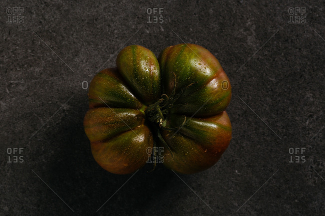 A wet green heirloom tomato on dark background