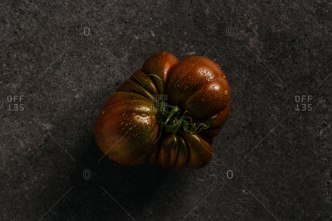 A wet red heirloom tomato on dark background