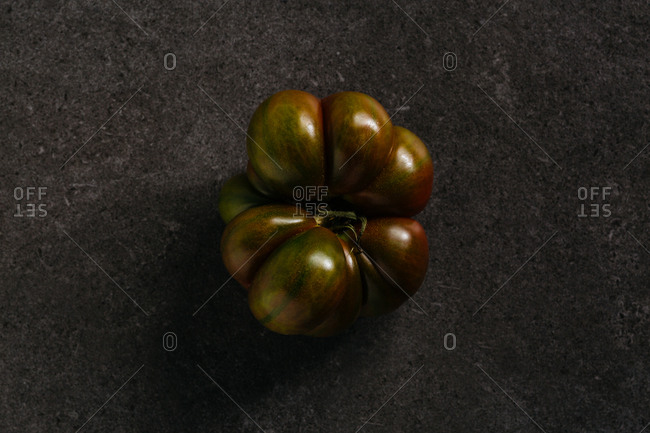 A lumpy green heirloom tomato on dark background