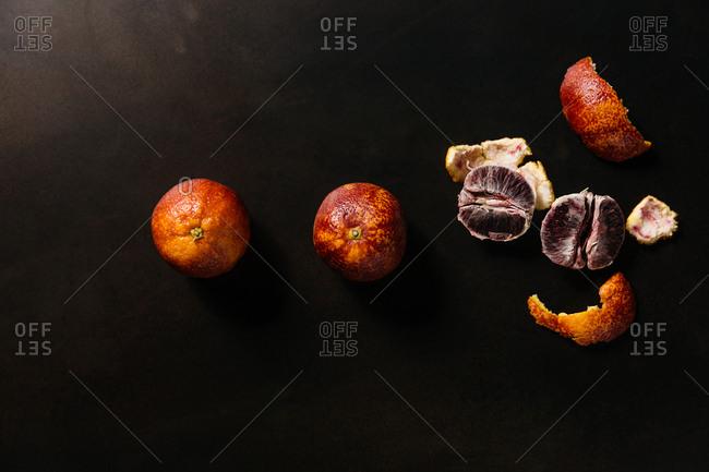 Three blood oranges on black background and one peeled