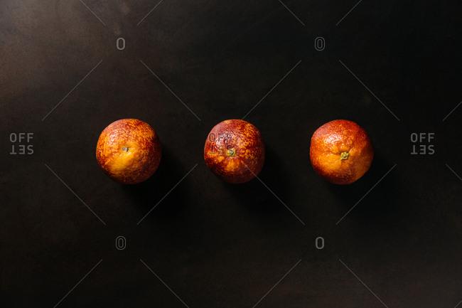Three blood oranges on black background