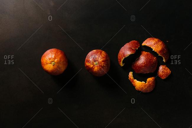 Blood oranges and peels on black background