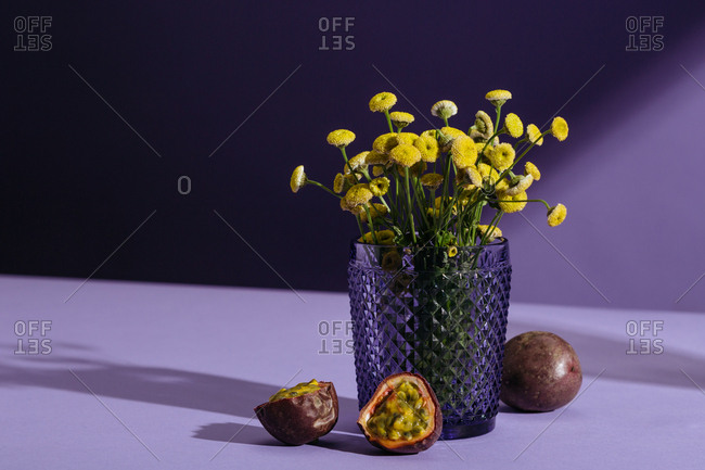 Passion fruit, tear drop grapes, chamomile flowers on purple background