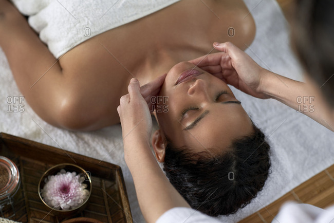 Beautiful woman having a facial treatment with professional therapist, relaxing zen peaceful