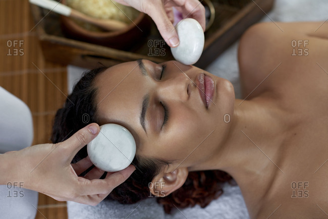 Relaxed woman in resort having a face massage with marble stones