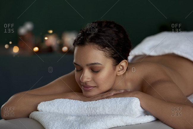 peaceful woman lying down on massage bed, waiting for her therapist in a zen calming environment