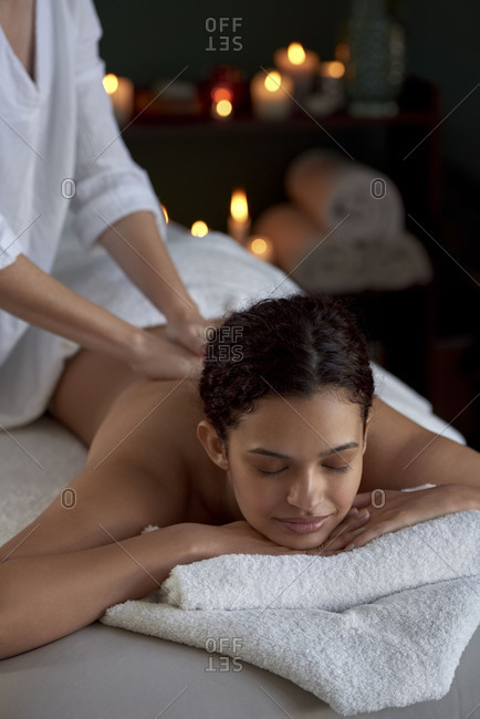 Hispanic woman enjoying a back massage, full body treatment at intimate cozy spa resort with trained professional practitioner