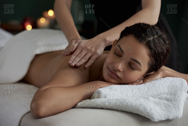 Tranquil peaceful scene in spa treatment room, woman enjoying full body massage