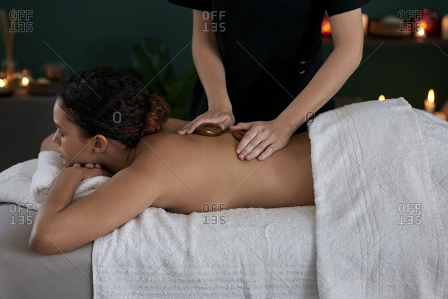 Woman lying down in cozy spa salon massage therapist using hot stone therapy technique