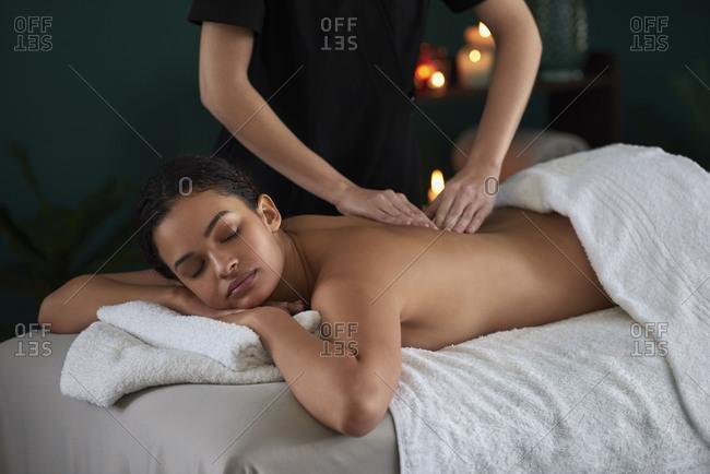 Beautiful mixed race hispanic latino woman enjoying a pressure point massage with trained professional in luxury spa salon