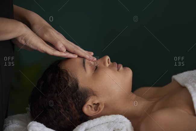 Close up of mixed race woman having a relaxing face massage, luxury pamper zen relaxing moment