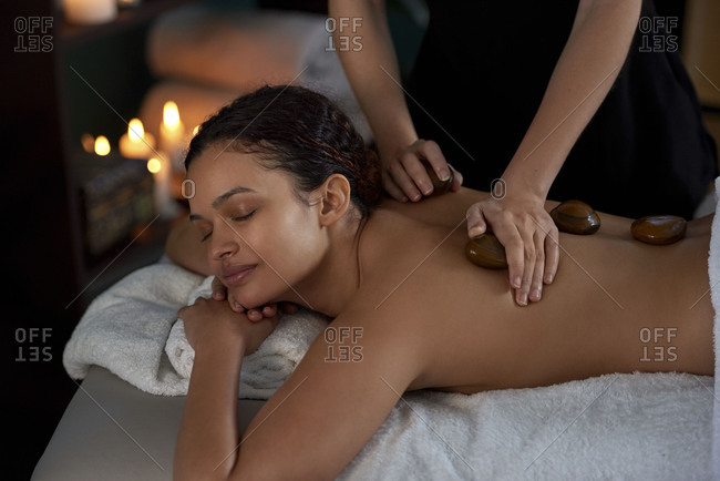 Beautiful woman enjoying relaxing hot stone massage by beauty therapist in cozy treatment room lit with candles